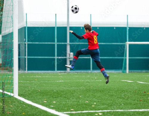 Leinwand Poster cute young boy in blue and red uniform jumps high ater the ball during football game on soccer field