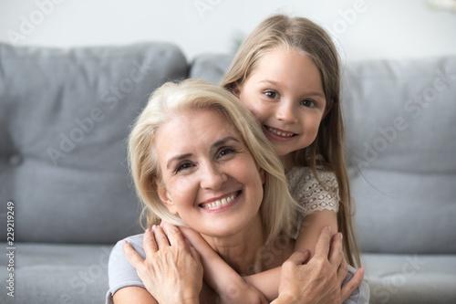 Tela Portrait of cute little granddaughter piggyback smiling grandmother posing for f
