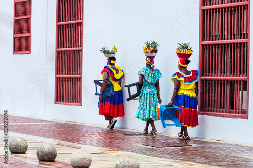 Traditional fruit street vendors in Cartagena de Indias called Palenqueras walking in front of the building of the town hall of Cartagena