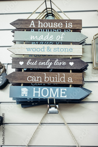 Hanging Composition of wooden painted breds with Motivational and inspirational quotes - Only love can build a home on the wall background. Vintage styled toning. Home comfort concept. Selective focus