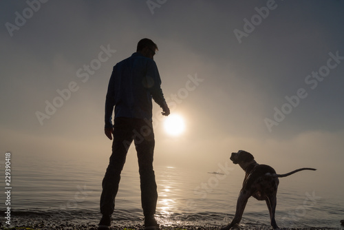 Silhouetted man and dog at the beach in heavy fog waiting to get his stick Fototapeta