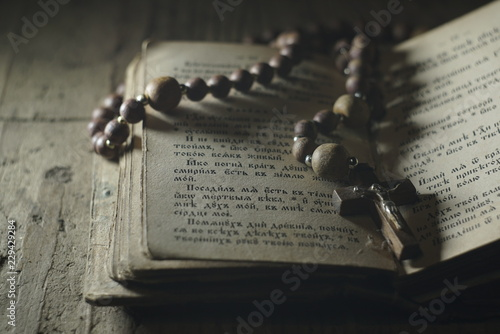 Fotografie, Tablou an old prayer book and wooden rosary in the dark