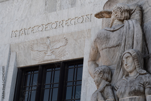Photo Text and an eagle carved into marble above the entrance to the Oregon State Capitol building in Salem, part of a marble relief carving representing white settlers in the foreground