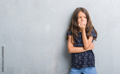 Young hispanic kid over grunge grey wall looking stressed and nervous with hands on mouth biting nails. Anxiety problem.