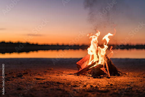Leinwand Poster Small campfire with gentle flames beside a lake during a glowing sunset