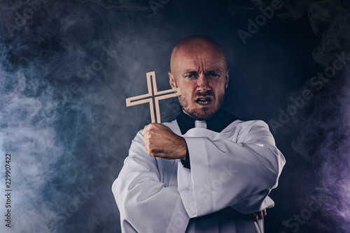 Canvas Print Catholic priest exorcist in white surplice and black shirt