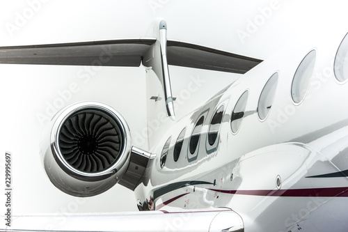 Fototapeta High detailed closeup view on small white private business jet windows engine