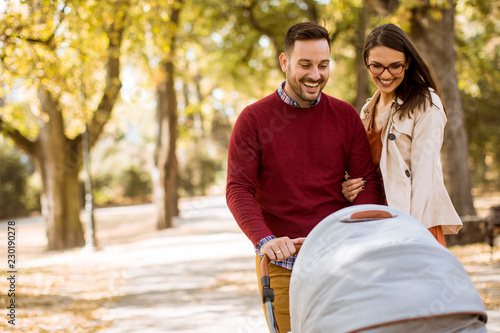 Obraz na płótnie Happy young parents walking in the park and driving a baby in baby carriage