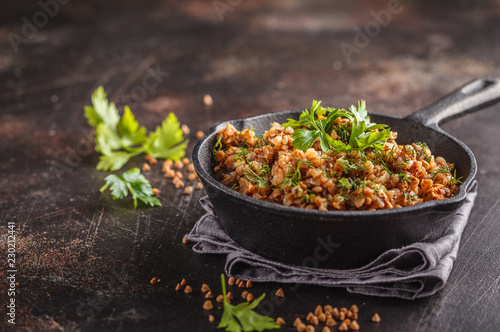 Buckwheat with meat in a cast iron pan on a dark background, copy space.