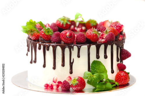 cake covered with berries of raspberry strawberry pomegranate mint leaves doused with chocolate on an isolated white background