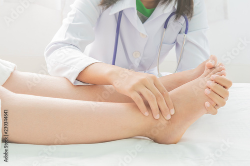 Fotografia Foot swelling in pregnant women and doctor on bed
