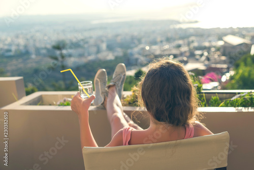 Cuadros en Lienzo Girl with a long hair in the headphones on the chair on the balcony listening to