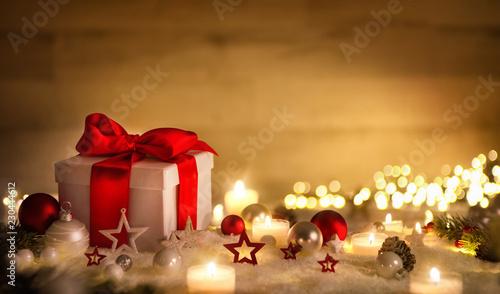 Weihnachten Hintergrund mit Geschenk und rotem Band, Kerzen, Lichterkette, Weihnachtsdeko und Schnee