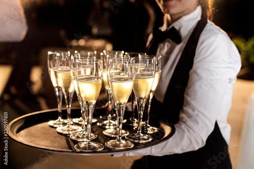 Foto cameriere con un vassoio pieno di calici con aperitivo di prosecco