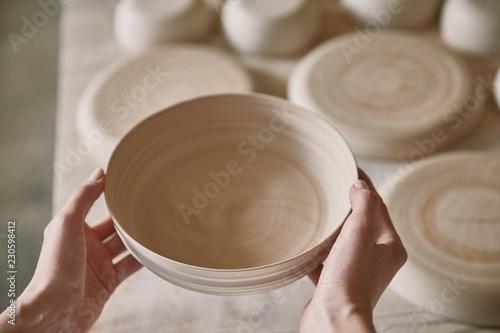 cropped image of woman holding ceramic dish at pottery studio Tapéta, Fotótapéta