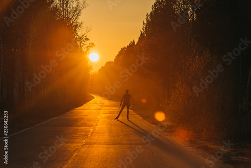 Training an athlete on the roller skaters. Biathlon ride on the roller skis with ski poles, in the helmet. Beautiful sunset silhouette. Autumn workout. Roller sport. Adult man riding on skates.