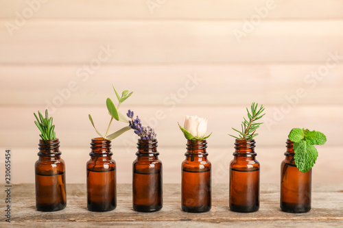 Glass bottles with different essential oils and herbs on wooden background