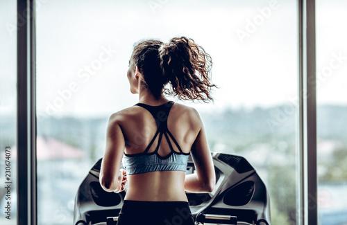 Atrakcyjna kobieta działa na bieżni w siłowni sportu, życia sportowego i sprzętu sportowego. Widok z tyłu.
