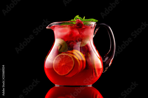 Glass jar of red wine sangria with wild berries and citrus mix isolated at black background Fototapeta