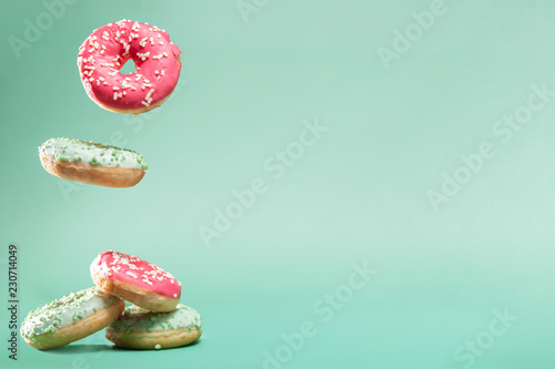 Slika na platnu Donuts with pink and green icing with sprinkles on mint backround with copyspace