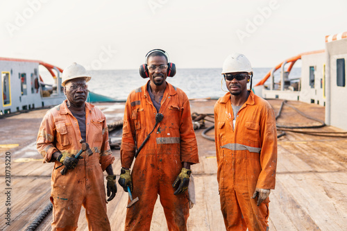 Fotografering Seamen crew AB or Bosun on deck of offshore vessel or ship , wearing PPE personal protective equipment - helmet, coverall, lifejacket, goggles