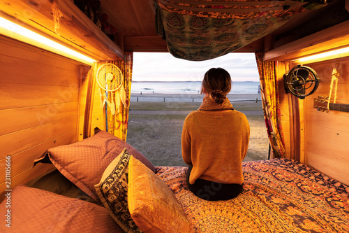 Tablou Canvas Woman watching sunset over beach from bohemian camper van in a van life theme