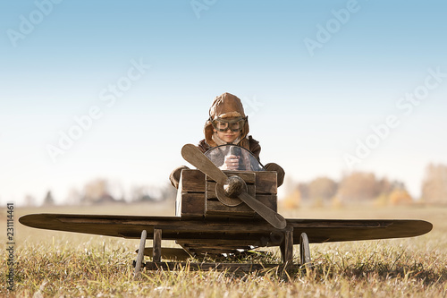 Portrait of the young aviator in a toy airplane child Fototapeta