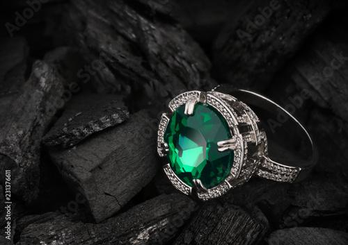 jewelry ring with big tourmaline gem on black coal background