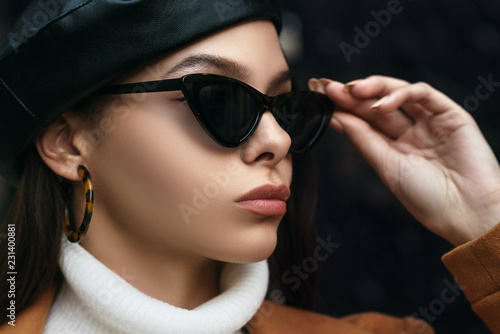 Outdoor close up fashion portrait of young beautiful woman wearing cat eye sunglasses, leopard print hoop earrings, leather beret. Model looking aside