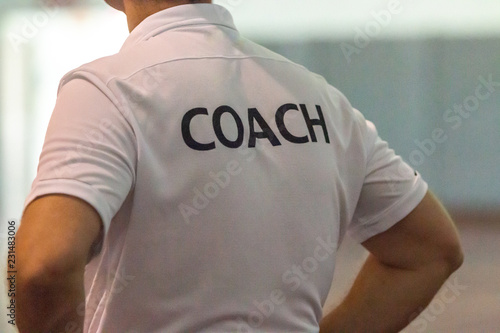 Back view of male sport coach with word COACH written on back of his shirt Poster Mural XXL