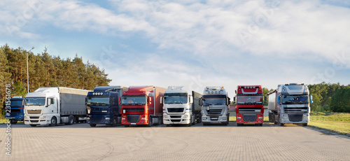 Photo A long range of various types and colors of trucks on a truck stop