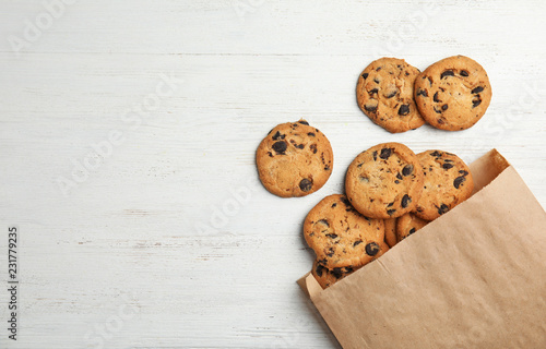 Paper bag with delicious chocolate chip cookies on wooden table, flat lay. Space for text