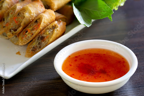 Sweet and spicy sauce for Veg. spring roll in white bowl on dark wooden table