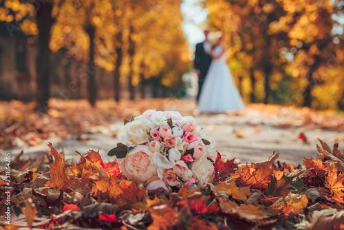 Wedding bouquet and wedding couple in orange park Fototapete