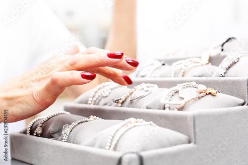 Biżuteria i dodatki. Kobieta ogląda biżuterię w salonie jubilerskim