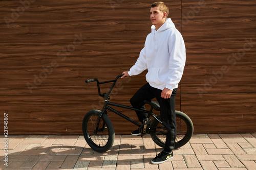 Valokuvatapetti Full length portrait of modern young man posing with bmx bike standing against w