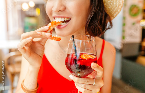 Happy Asian woman in hat eating local Spanish cuisine grilled seafood