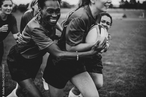 Energetic female rugby players on the field