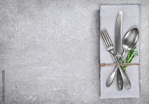 Table setting background with copy space. Concrete background with napkin, silverware and rosemary branch. Cutlery with fork, knife and spoon. Top view.