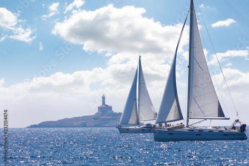 Fototapeta two sailing ships near a lighthouse in summer day, Croatia