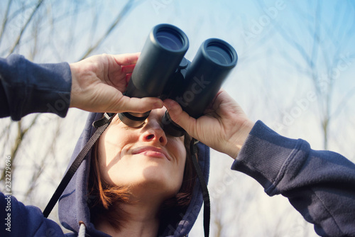 Fotografia Girl with the field-glass watches birds
