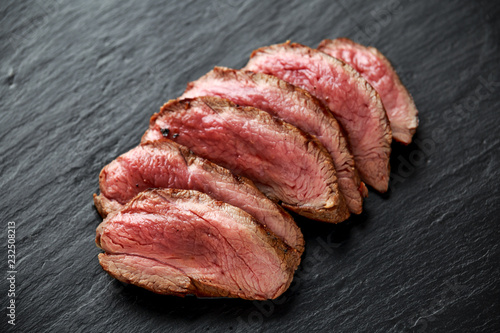 Fotografija Medium rare venison steak on rustic dark stone board