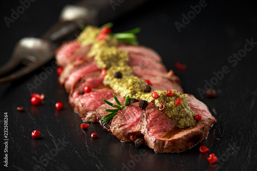 Medium rare venison steak with green pesto sauce and pepper Fototapeta