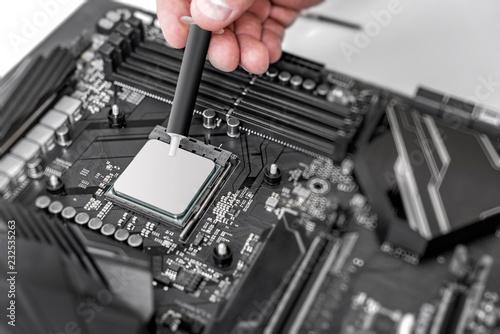 Fototapeta Engineer applying thermal paste on the computer board chip cpu.