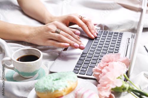 Relaks o poranku.  Kobieta pisze na komputerze leżąc na łóżku.