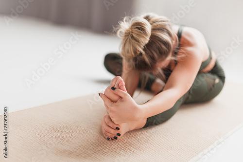 Young woman performing Janusirsasana exercise Fototapeta