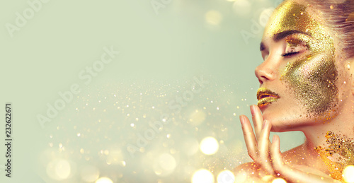 Beauty fashion model girl with golden skin makeup and body, golden jewelery background. Gold body art. Fashion art portrait