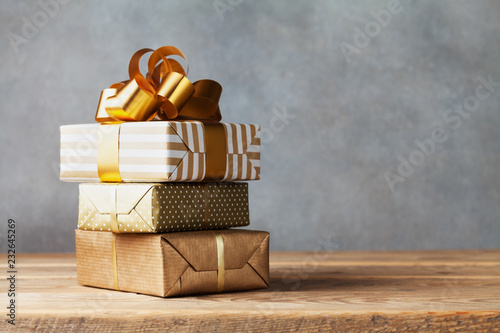Heap of golden gift or present boxes on wooden table. Composition for birthday or christmas.