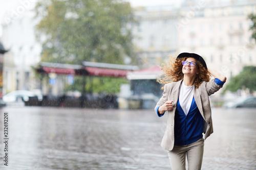 Fotografiet Happy young woman in casualwear running down boulevard in the rain