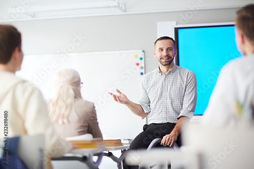 Obraz na plátně Happy confident teacher explaining his students what he thinks about new subject